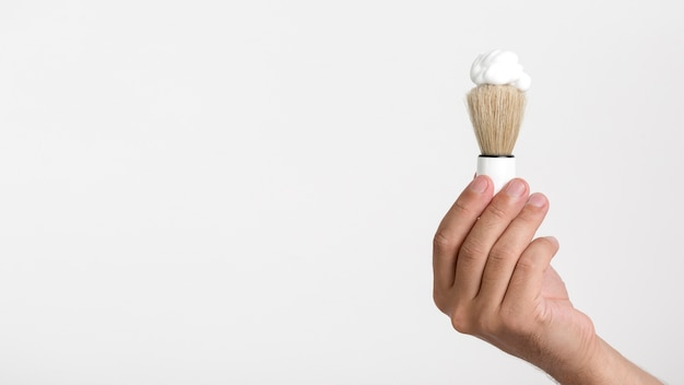 Hand holding shaving brush with foam over white background