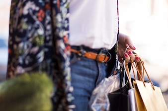 Hand holding shopping bags outdoors