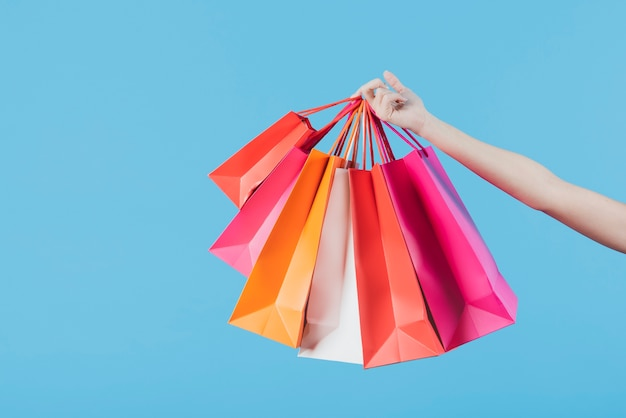 Hand holding shopping bags on plain background