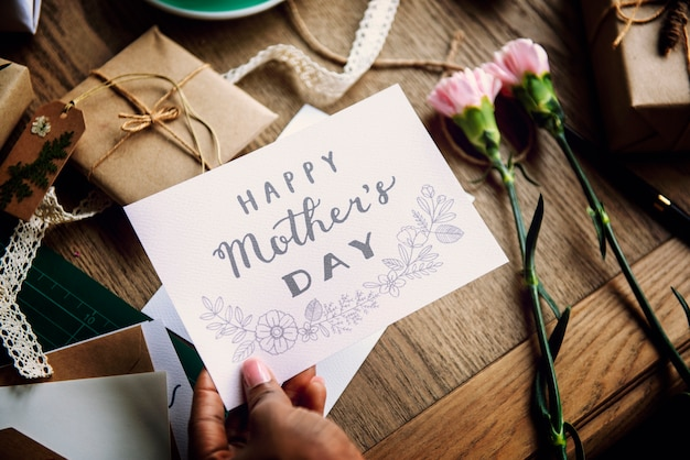 Hand holding show happy mother day card with flowers background