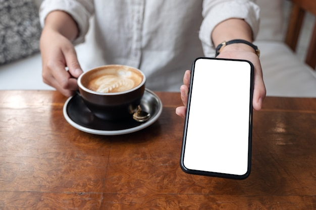 Hand holding and showing black mobile phone with blank white desktop screen to someone while drinking coffee