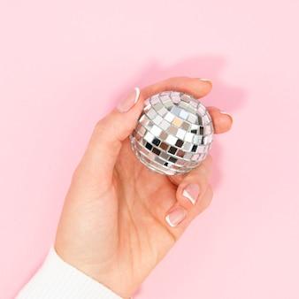 Mano che tiene la palla da discoteca d'argento