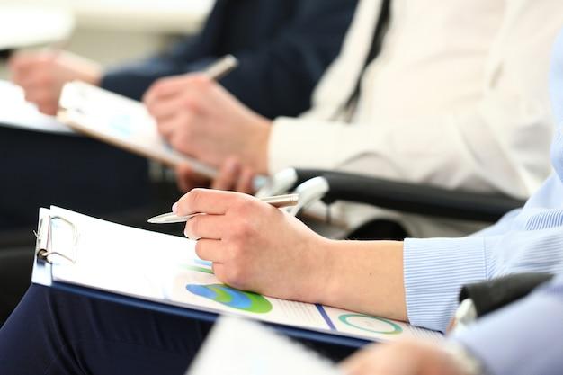 Рука, держащая серебряную ручку и блокнот с документом статистики