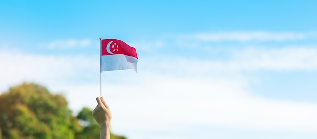 Hand holding singapore flag on blue sky background. singapore national day and happy celebration concepts