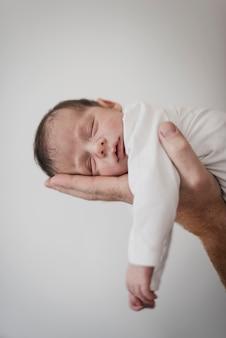 Hand holding sleepy little baby
