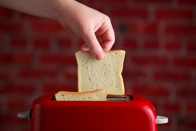 Рука кусок хлеба в красном тостере на фоне стены кирпичей. кухонная утварь