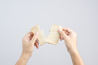 Hand holding sliced whole grain bread