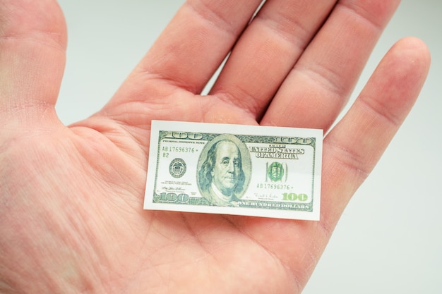 Hand holding small banknote of us dollar