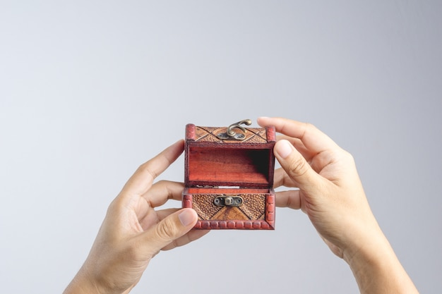 Hand holding small leather treasure chest box