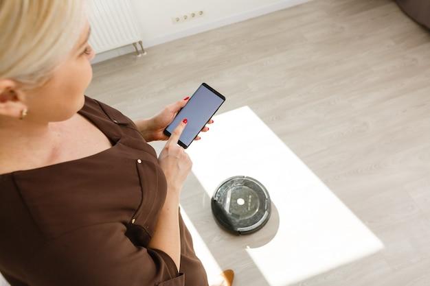 스마트 폰을 들고 실내의 현대적인 실내에서 백그라운드에서 무선으로 충전된 장치를 들고 있습니다. 개념 첨단 기술, 수직