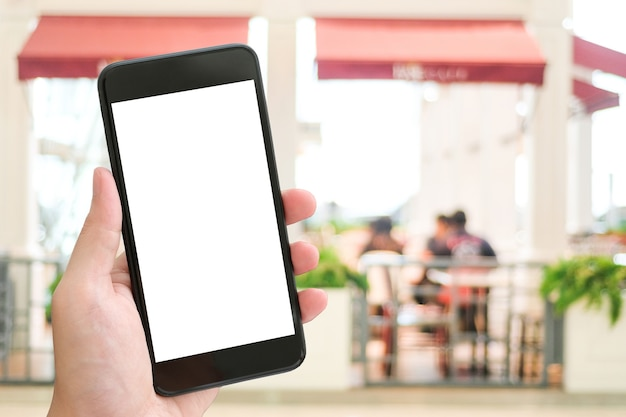 Hand holding smart phone over blur restaurant background