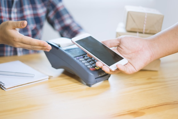 Hand holding smart phone over credit card machine