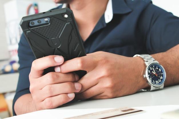 スマートフォンや携帯電話を持っている手。ワーキングオフィスのコンセプト。デジタル決済の概念。サラリーマン。アカウントまたは財務。購入または購入者の概念。オンラインショッピング。