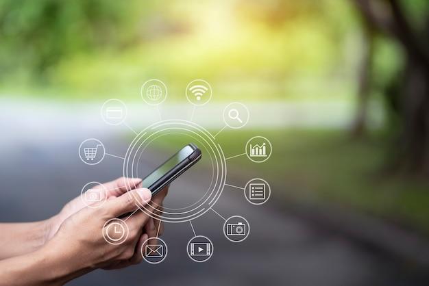 Рука, держащая смарт-телефонные платежи, покупки в интернете с графическим значком, подключение к сети клиента