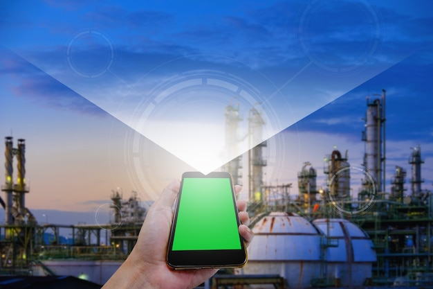 Hand holding of smart phone shows technology graphics control work on blurred industrial background