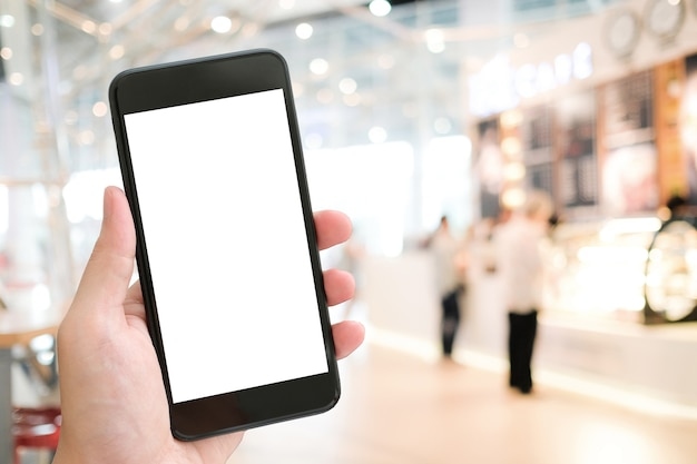 Hand holding smart phone with blank on screen over blur restaurant background