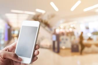 手、スマートフォン、ぼやけたショッピングモールの背景
