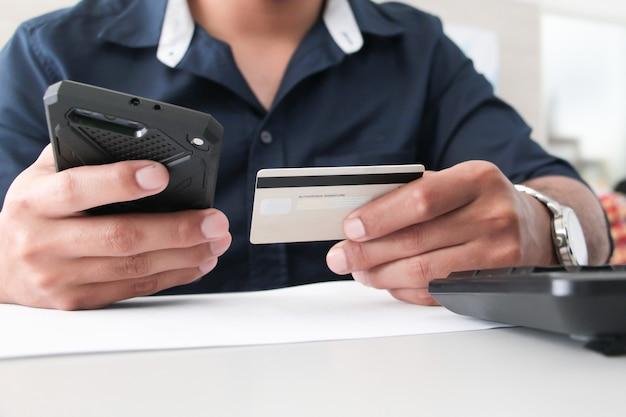 オフィスでクレジットカードまたはatmでスマートフォンを持っている手。ワーキングオフィスのコンセプト。デジタル決済の概念。サラリーマン。アカウントまたは財務。購入または購入者の概念。