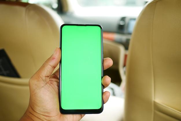 차에 빈 화면이 있는 스마트 폰을 들고 있는 손