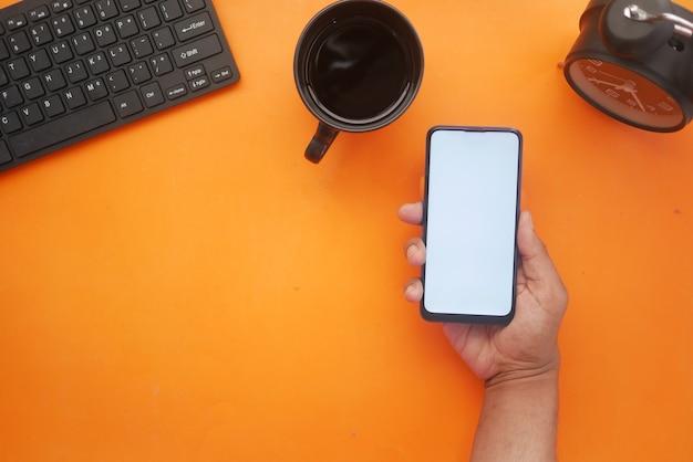 Рука держит смартфон с пустым экраном на оранжевом фоне