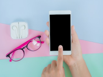 Hand holding smartphone and press, glasses and earphone on colorful table.