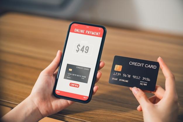 スマートフォンを持っているとオンラインでクレジットカードによる支払いとオンラインショッピングアプリケーションを使用する手。
