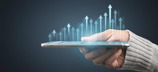 スマートフォンデバイスを持って画面に触れている手。証券取引所市場の概念。グラフ分析キャンドルで見ているトレーダー