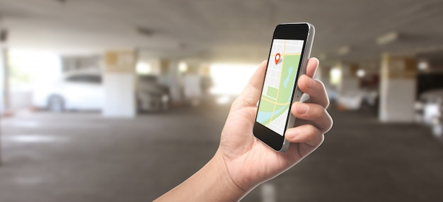 Hand holding smartphone device and touching screen, which is a red icon of the location, concept of online navigation