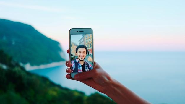 海の前で男とビデオ通話中にスマートフォンを持っている手は、baの美しい風景...