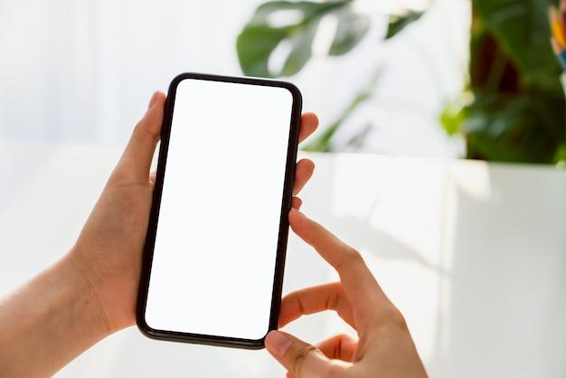 テーブルに空白の画面のスマートフォンのモックアップを持っている手。