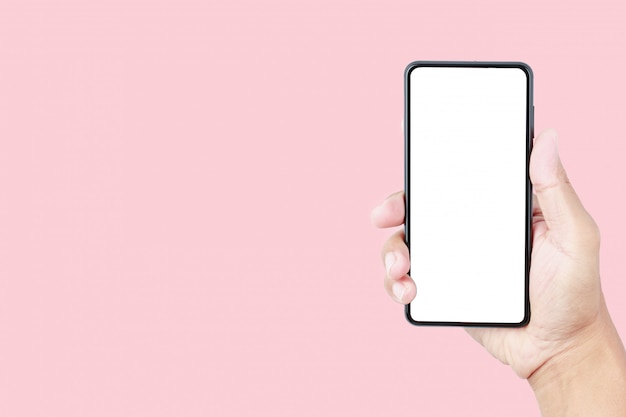 Hand holding smartphone mockup on pink pastel background with copy space
