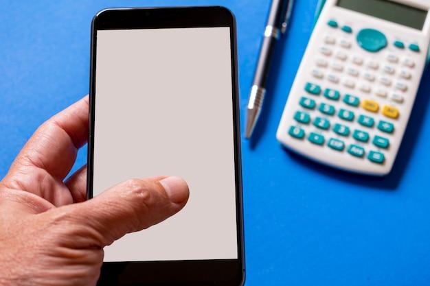 Рука смартфон на столе с калькулятором и ручкой.