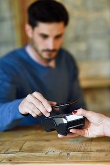 Hand holding smartphone paying on edc machine.