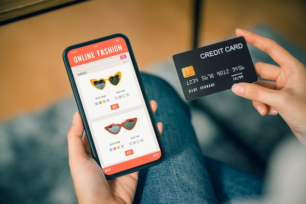 Hand holding smartphone and using application shopping online with payment by credit card online.