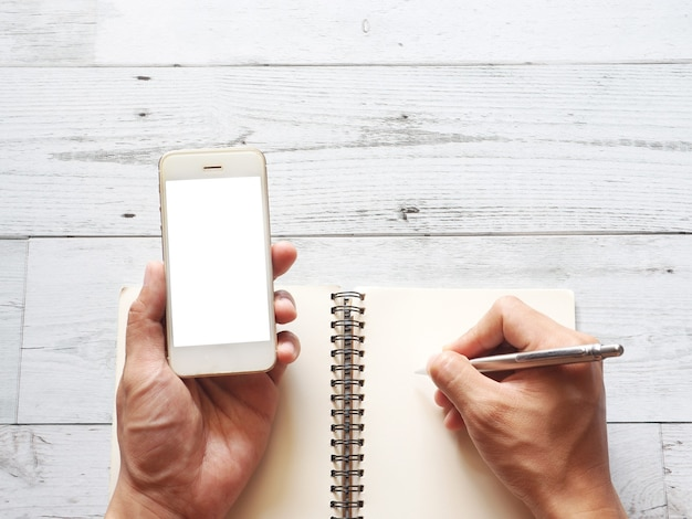 Hand holding smartphone white display and write on blank page notebook on white wood table top view