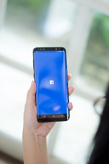 Hand holding smartphone with application facebook