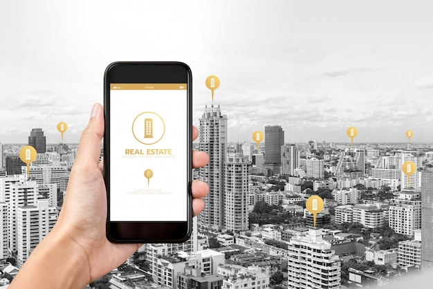Hand holding smartphone with application to find  real estate on screen