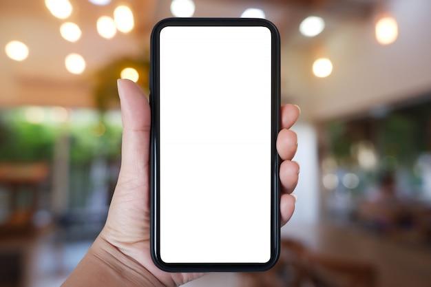 카페 인테리어에 응용 프로그램에 대 한 빈 화면이 스마트 폰 들고 손