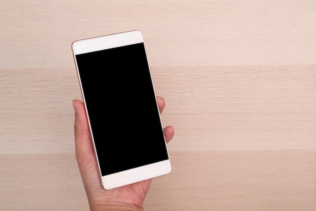 Hand holding smartphone with blank screen isolated on wooden background