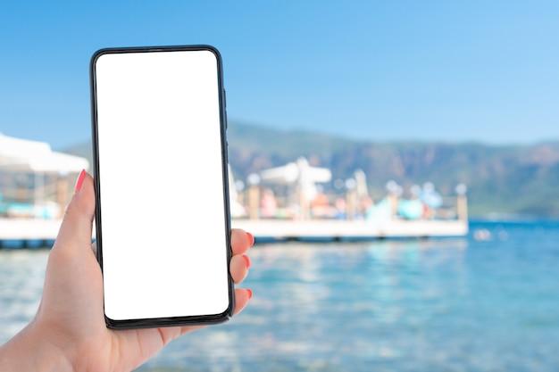 海と青い空の上に空白の画面でスマートフォンを持っている手。