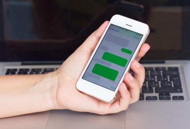 Рука держит смартфон с пустыми облаками sms на фоне ноутбука
