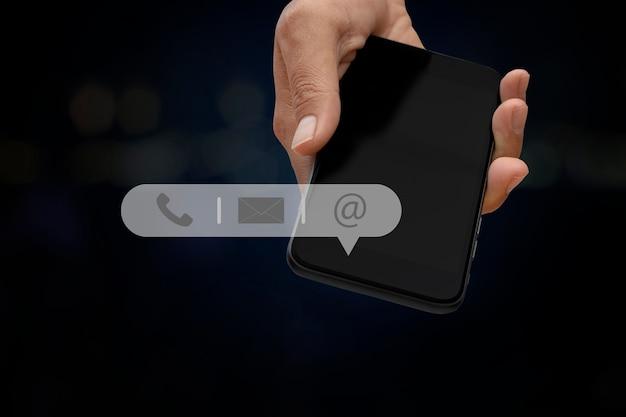 아이콘 전화, 메일, 주소가 있는 스마트폰을 들고 있는 손. 고객 지원 서비스는 저희에게 개념에 문의하십시오. 복사 공간입니다.