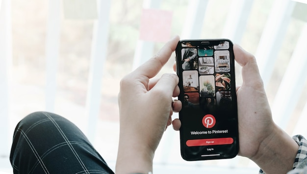 Hand holding smartphone with pinterest app on the screen. pinterest is an online pinboard that allows people to pin their interesting things