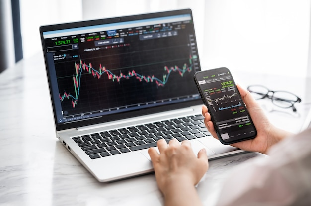 Hand holding smartphone with stock market data and using laptop display graph and chart for analyze and check before trading stocks online