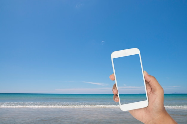 Hand holding of smartphone with tropical sea and beach as background