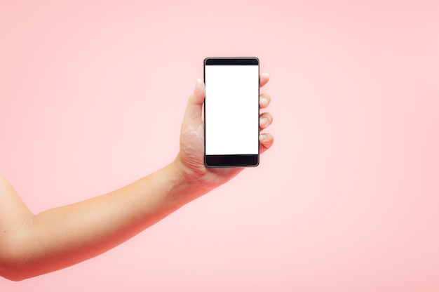 Hand holding smartphone with white blank screen on pink background