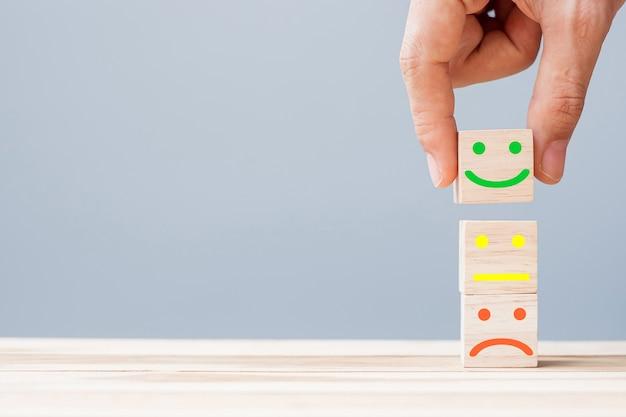 木製のブロックに笑顔の顔のシンボルを持っている手