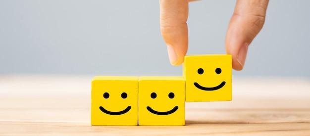 Рука, держащая символ улыбки на желтых деревянных блоках
