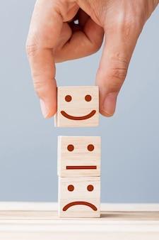 Hand holding smile face symbol on wooden blocks