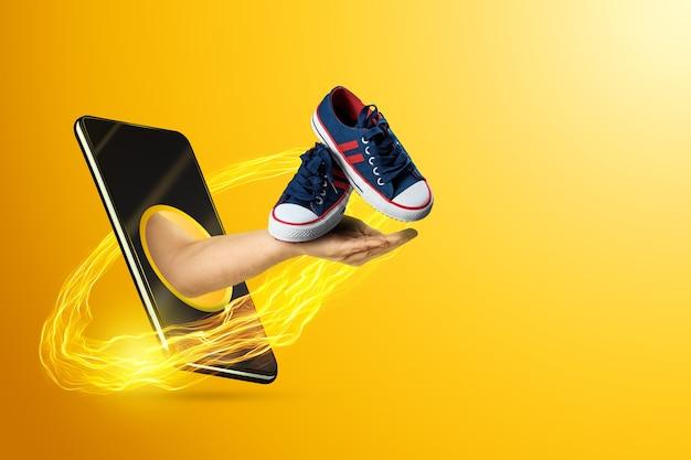 Рука держит кроссовки через смартфон